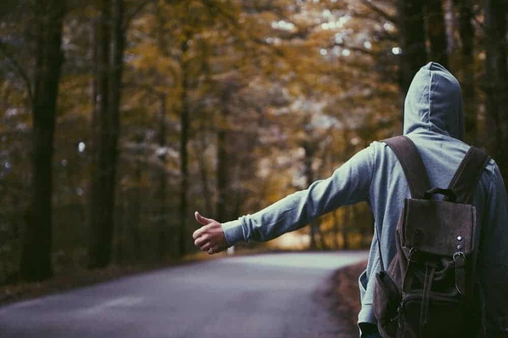 ragazzo fa autostop su una strada alberata - limiti per la felicità